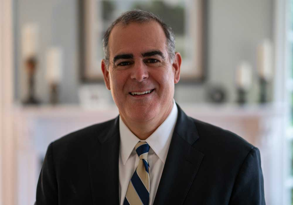 Headshot of Richard Milone wearing black blazer and gold-and-blue tie