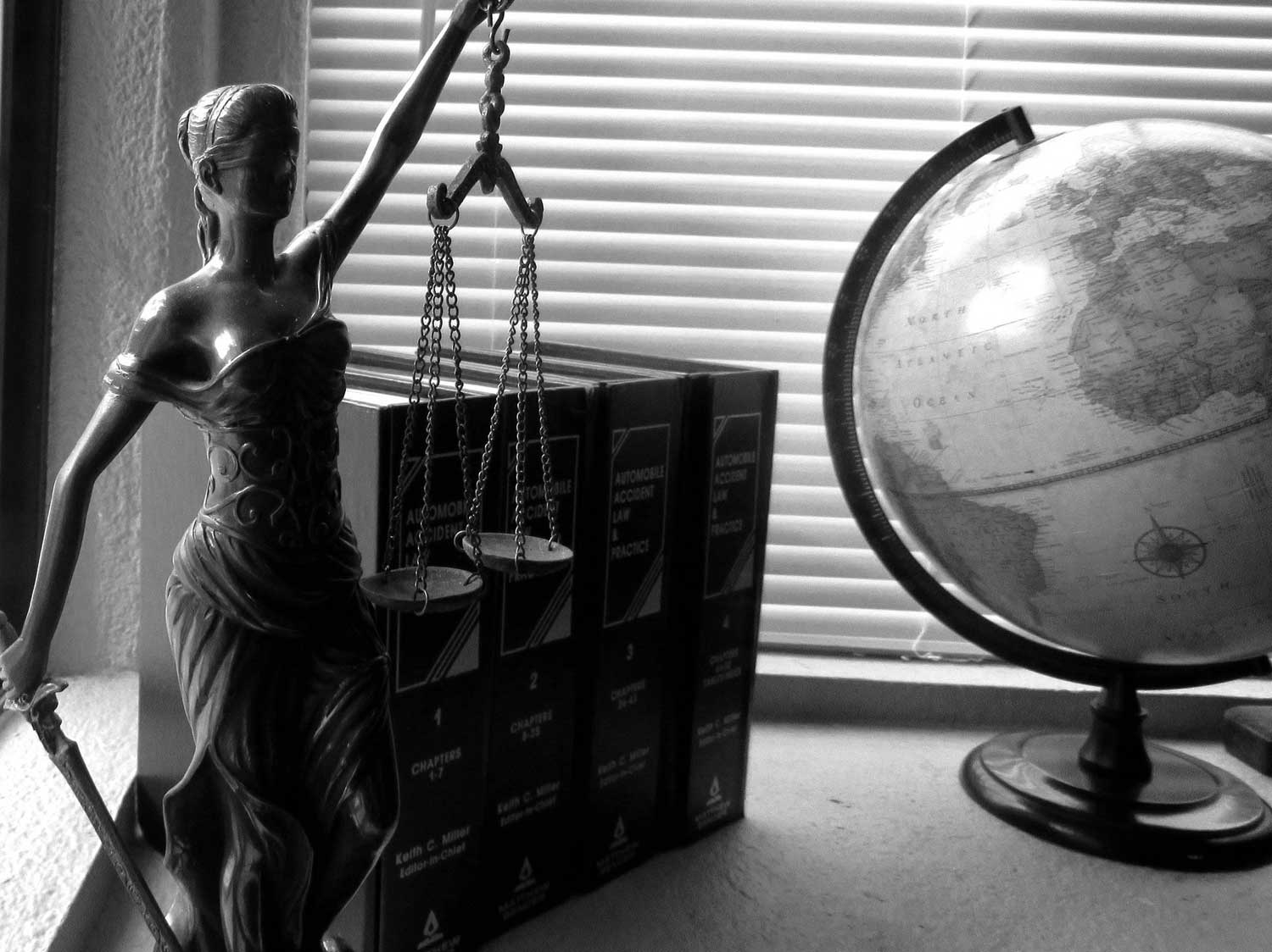 Black-and-white photo of Lady Justice figure in front of 4 law books next to a globe
